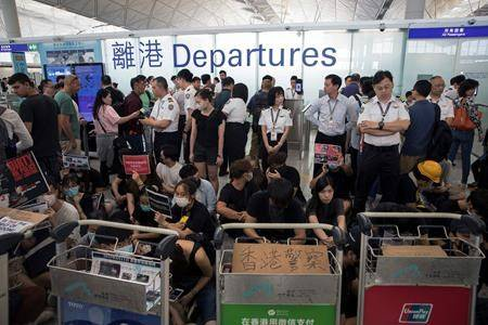 Airport security personnel stand guard as travelers walk past protesters holding a sit-in rally at the departure gate of the Hong Kong International Airport in Hong Kong, Tuesday, Aug. 13, 2019. (AP Photo/Vincent Thian)