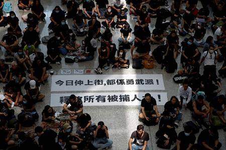 """Protesters surround banners that read: """"Those on the street today are all warriors!"""" center top, and """"Release all the detainees!"""" during a sit-in rally at the arrival hall of the Hong Kong International airport in Hong Kong, Monday, Aug. 12, 2019. (AP Photo/Vincent Thian)"""