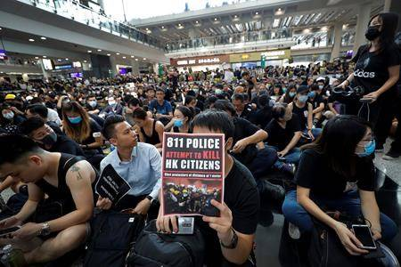 In this Monday, Aug. 12, 2019, photo, a man holds a placard as thousands of protesters take part in a sit-in rally at the arrival hall of the Hong Kong International Airport, a major hub in Asia, in Hong Kong. (AP Photo/Vincent Thian)