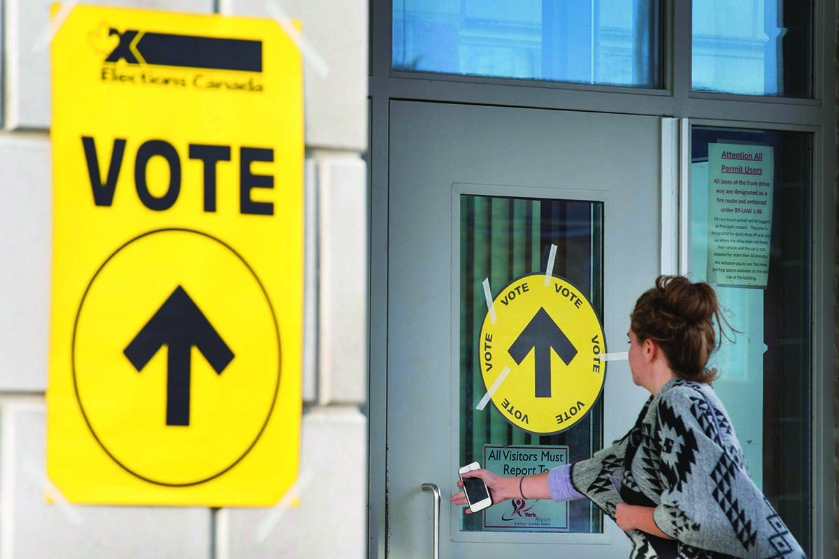 Stephane Perrault, the acting chief electoral officer, says Elections Canada must stay above the political fray and should not be perceived as being involved in anything that could influence the outcome of a campaign. A woman enters Maple High School in Vaughan, Ont., to cast her vote in the Canadian federal election on Monday, Oct. 19, 2015. THE CANADIAN PRESS/Peter Power