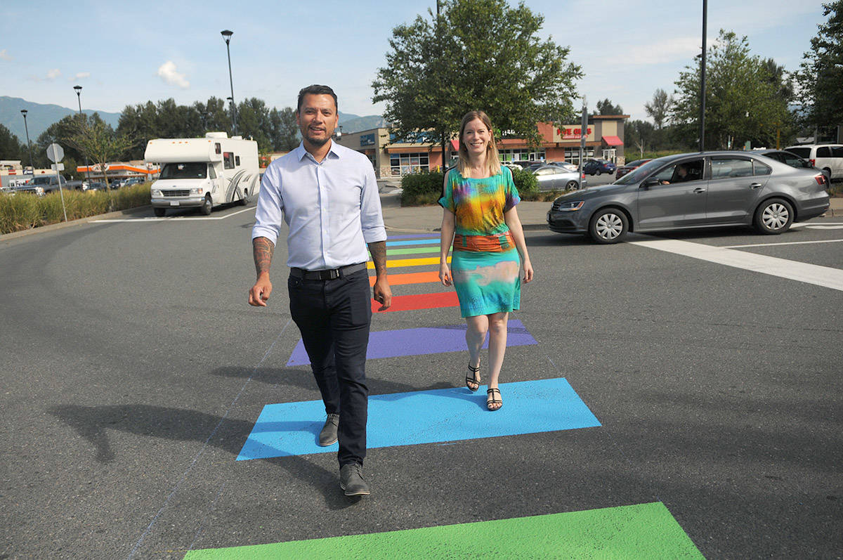 Squiala Chief David Jimmie walks with Amber Price through one of two freshly painted rainbow crosswalks at Eagle Landing shopping centre in Chilliwack on Tuesday morning. Price is a downtown Chilliwack business owner who recently hand delivered a petition to city hall with 14 other supporters who want a rainbow crosswalk installed on Wellington Avenue. She was at Eagle Landing that day to personally thank Chief Jimmie. (Jenna Hauck/ The Progress)
