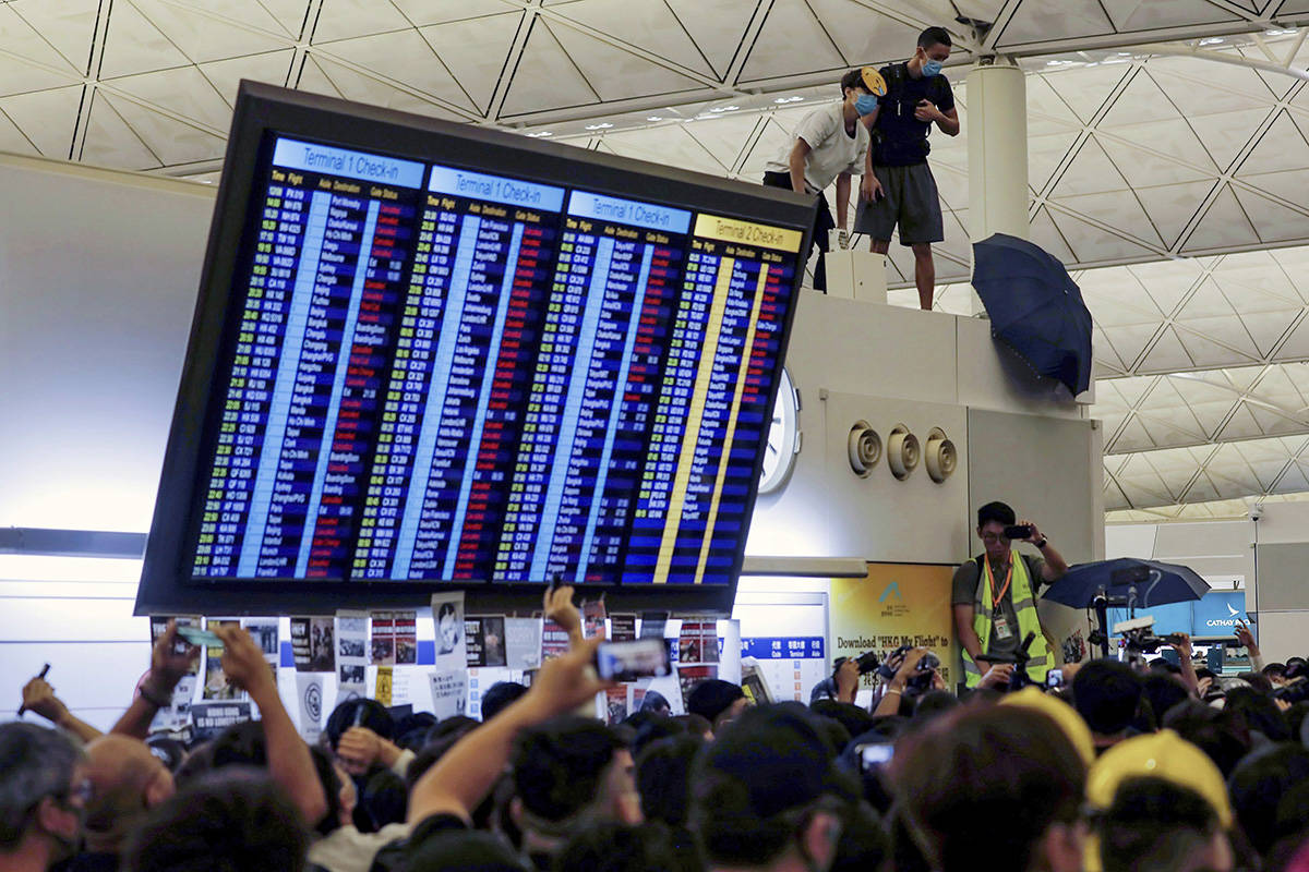 Protester use an umbrellas to block surveillance cameras during a demonstration at the Airport in Hong Kong, Tuesday, Aug. 13, 2019. Prominent human rights activists and Chinese political dissidents warned Tuesday about the potential for a brutal crackdown on protesters in Hong Kong. THE CANADIAN PRESS/AP-Vincent Yu
