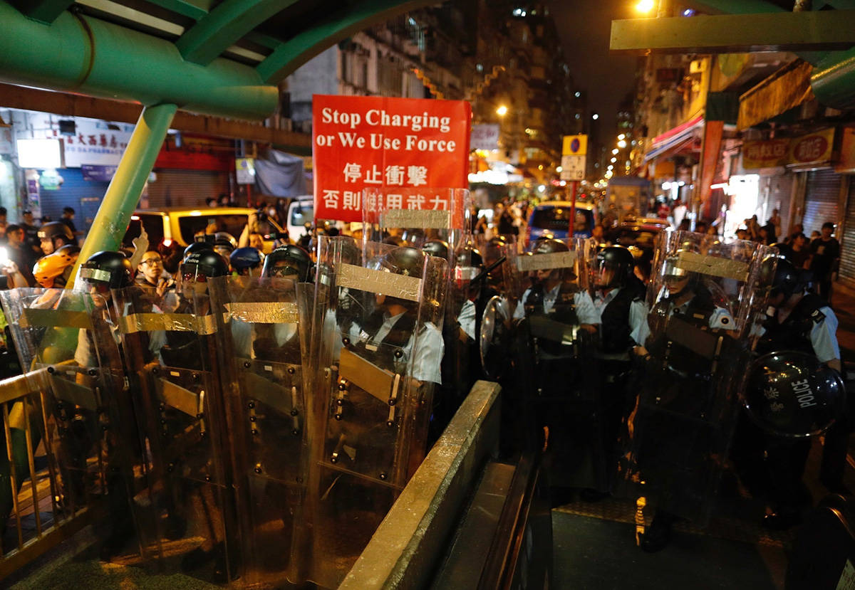 Police move out from the Shum Shui Po police station to confront protesters in Hong Kong on Wednesday, Aug. 14, 2019. German Chancellor Angela Merkel is calling for a peaceful solution to the unrest in Hong Kong amid fears China could use force to quell pro-democracy protests.(AP Photo/Vincent Yu)