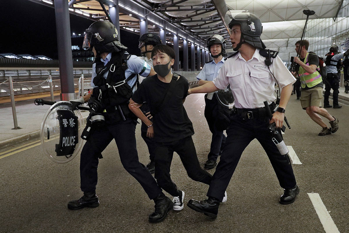 """Policemen arrest a protester during a clash at the Airport in Hong Kong, Tuesday, Aug. 13, 2019. The federal government is warning Canadians about travelling to Hong Kong amid massive protests and the Chinese military amassing on the border. The travel advisory went up around 9:30 ET this morning telling Canadians to """"exercise a high degree of caution in Hong Kong due to ongoing large-scale demonstrations.""""THE CANADIAN PRESS/AP, Vincent Yu"""