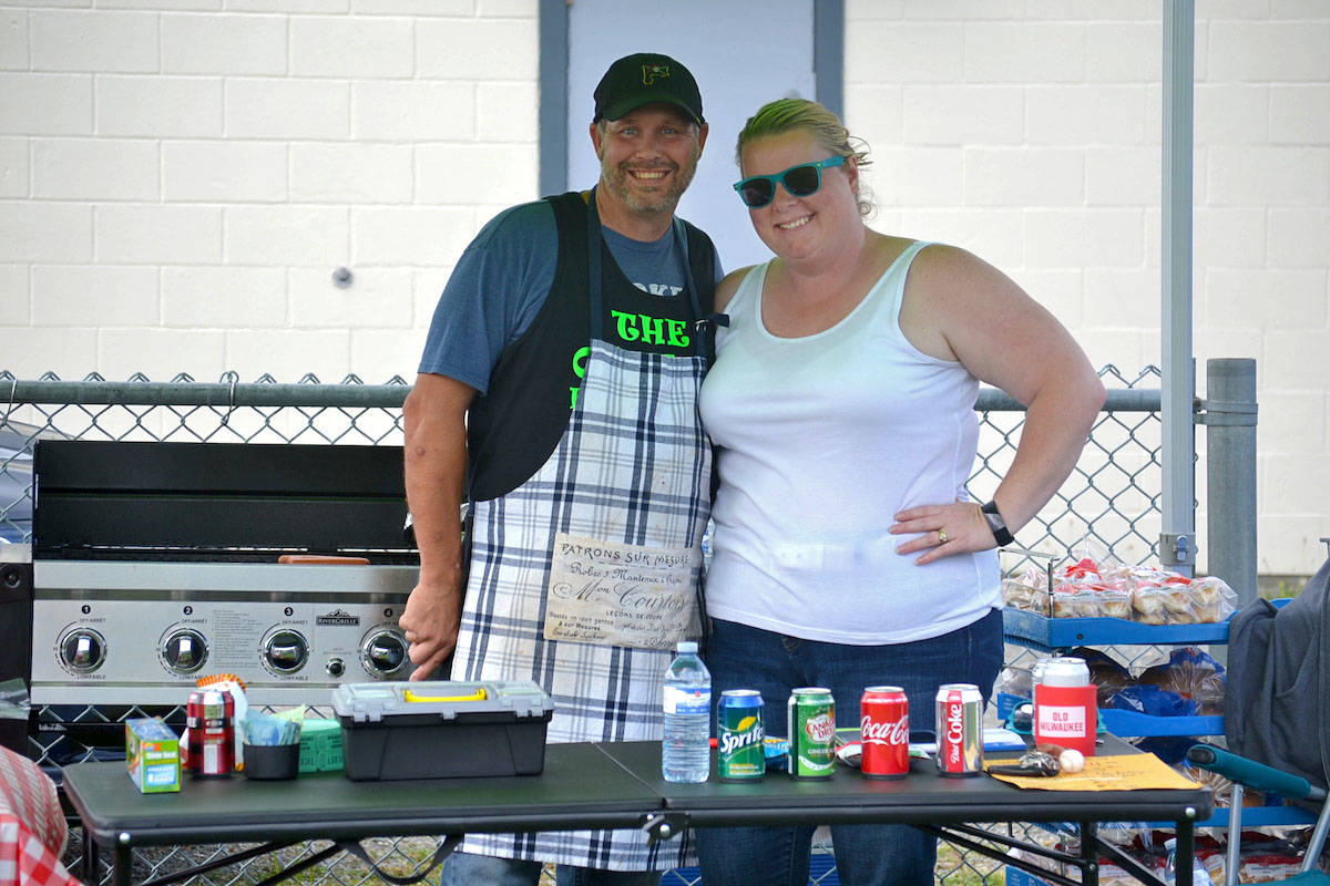 Volunteers Jen and Sean Gallawan, current Aldergrove slo-pitch players, cooked patties on a barbeque, donated by Save-On-Foods along with chips, soda, water, buns, and more. (Sarah Grochowski photo)
