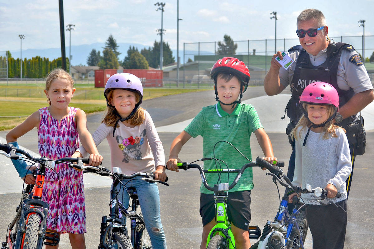 Young cyclists and friends Emma (from left) Sophia, Jack and Mia – all students at North Otter Elementary School – were given free passes to the water park by Cpl. Neuman (right) for wearing helmets while riding at the Aldergrove skateboard park this month. (Sarah Grochowski photo)