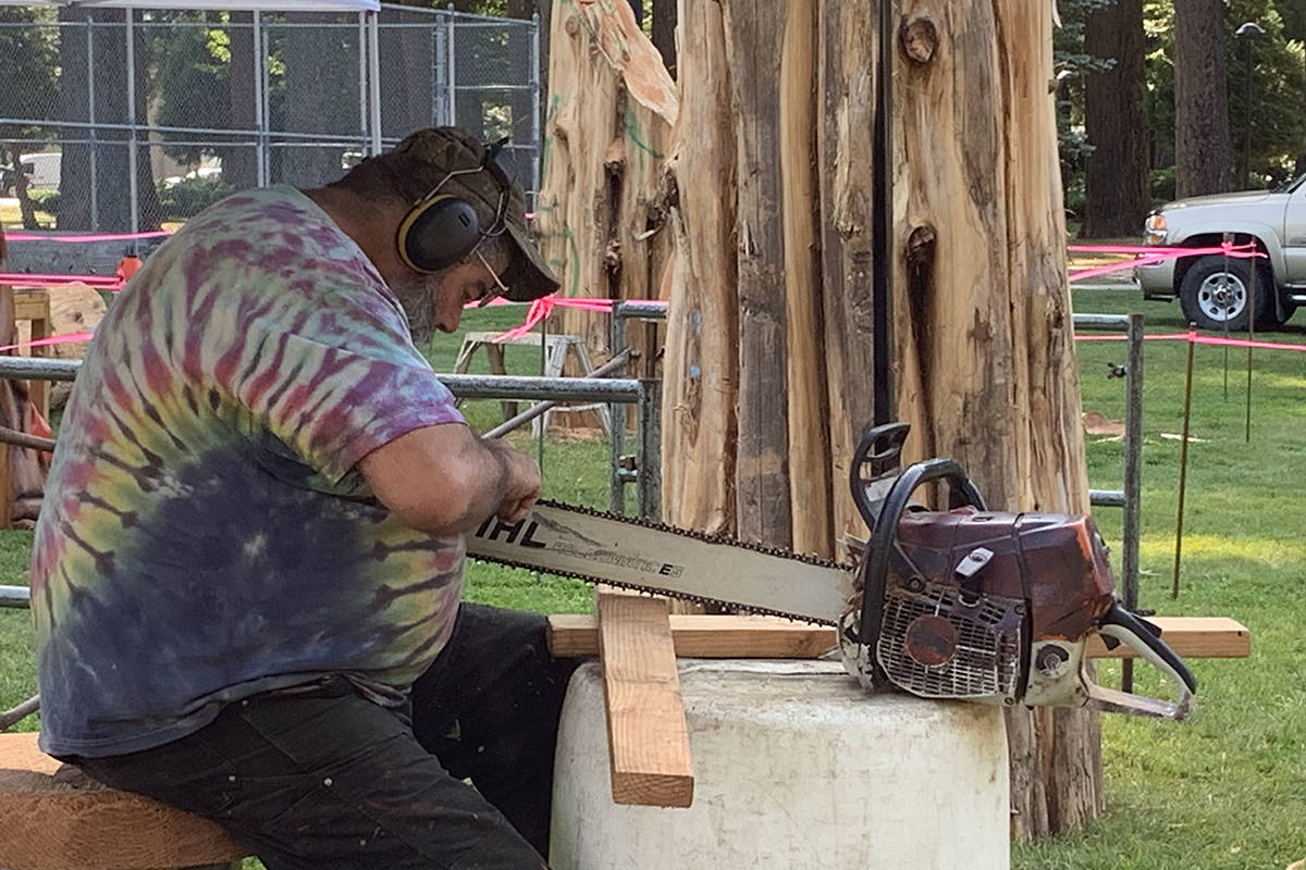 Steve Backus sharpens the blades on one of his chainsaws as carvers around him begin to work on their pieces, on the first morning of the 2019 Chainsaw Carving Competition in Hope Memorial Park on Thursday morning. (Jessica Peters/ Black Press)