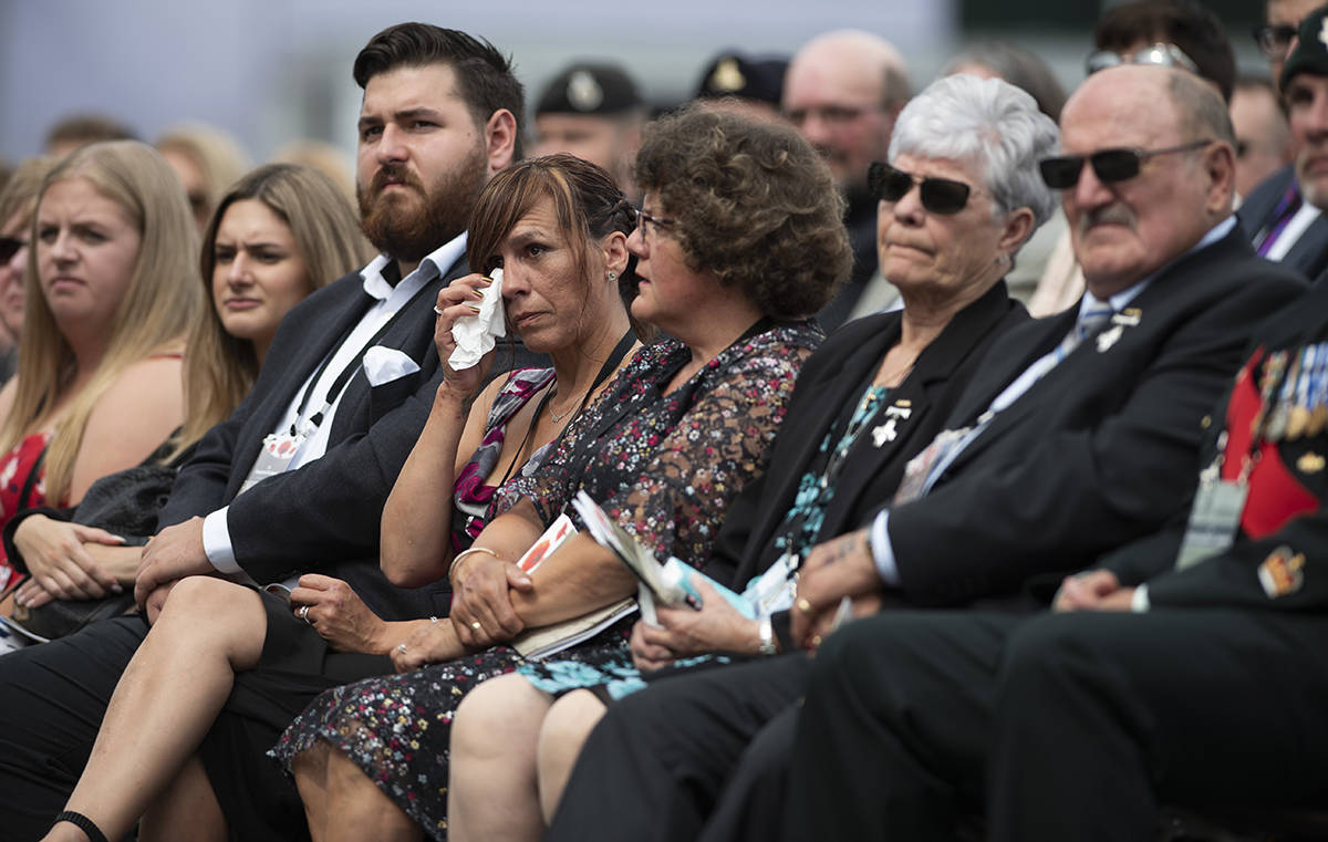 A guest wipes her eye during the rededication ceremony of the Kandahar cenotaph at National Defence Headquarters (Carling) in Ottawa on Saturday, Aug. 17, 2019. THE CANADIAN PRESS/Justin Tang