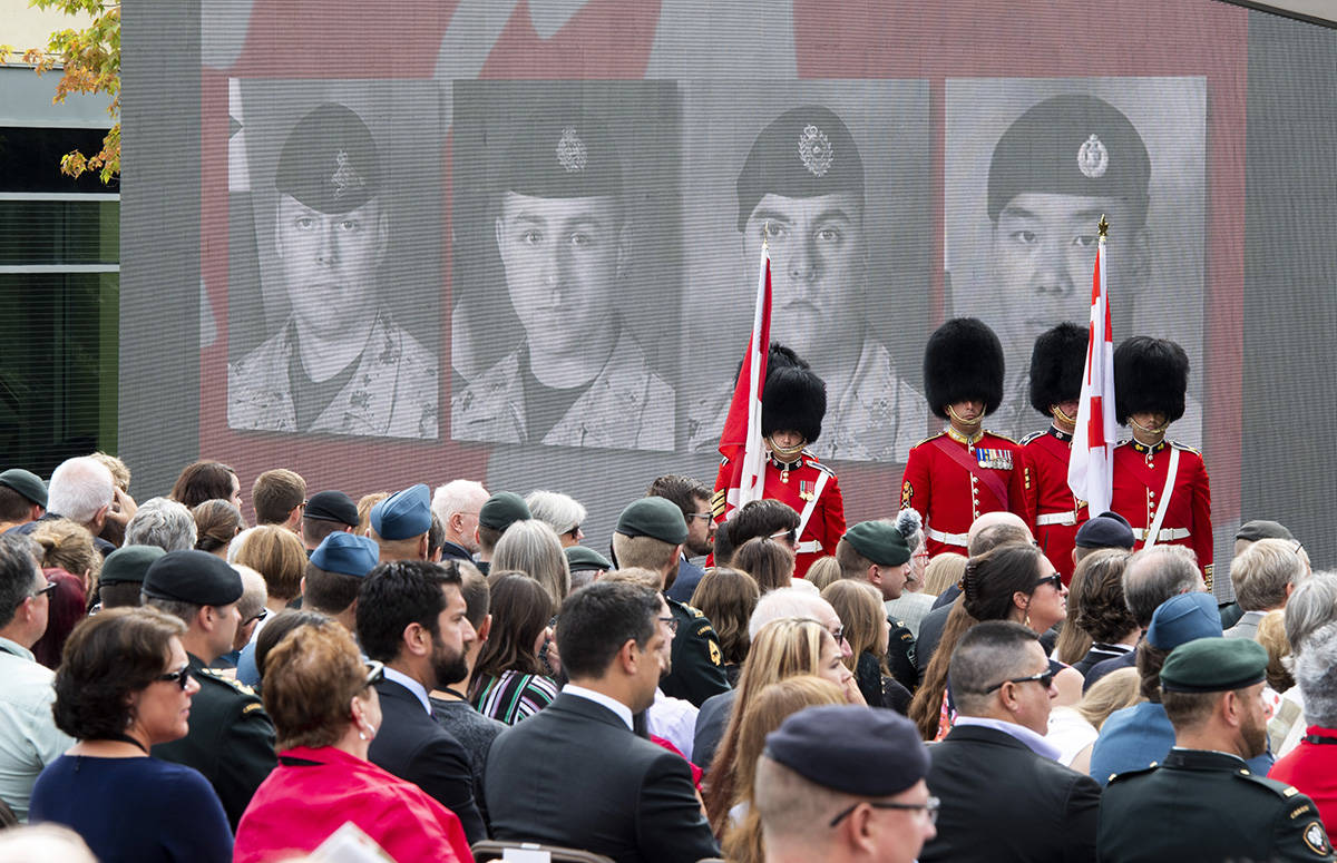 Faces of the fallen are shown on a screen during the rededication ceremony of the Kandahar cenotaph at National Defence Headquarters in Ottawa on Saturday, Aug. 17, 2019. THE CANADIAN PRESS/Justin Tang