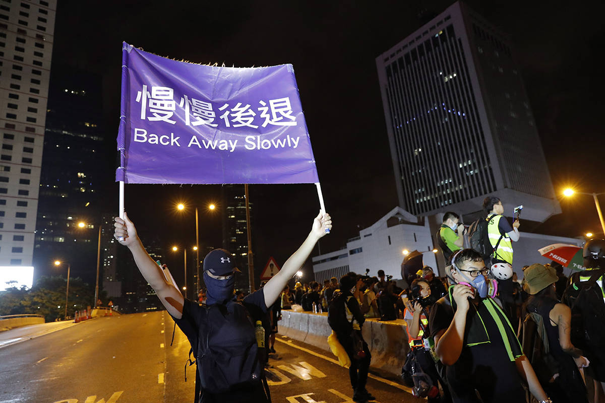 """A demonstrator holds a sign reading """"Back away slowly"""" to encourage other demonstrators to leave, near the Chinese Liaison Office in Hong Kong, Sunday, Aug. 18, 2019. Protesters turned Hong Kong streets into rivers of umbrellas Sunday as they marched through heavy rain from a packed park and filled a major road in the Chinese territory, where mass pro-democracy demonstrations have become a regular weekend activity this summer. (AP Photo/Vincent Thian)"""