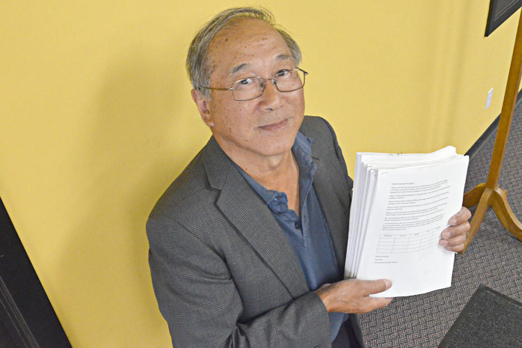 Gary Hee with the thousands of signatures he's accumulated against paid parking at hospital emergency rooms. (Matthew Claxton/Langley Advance Times)