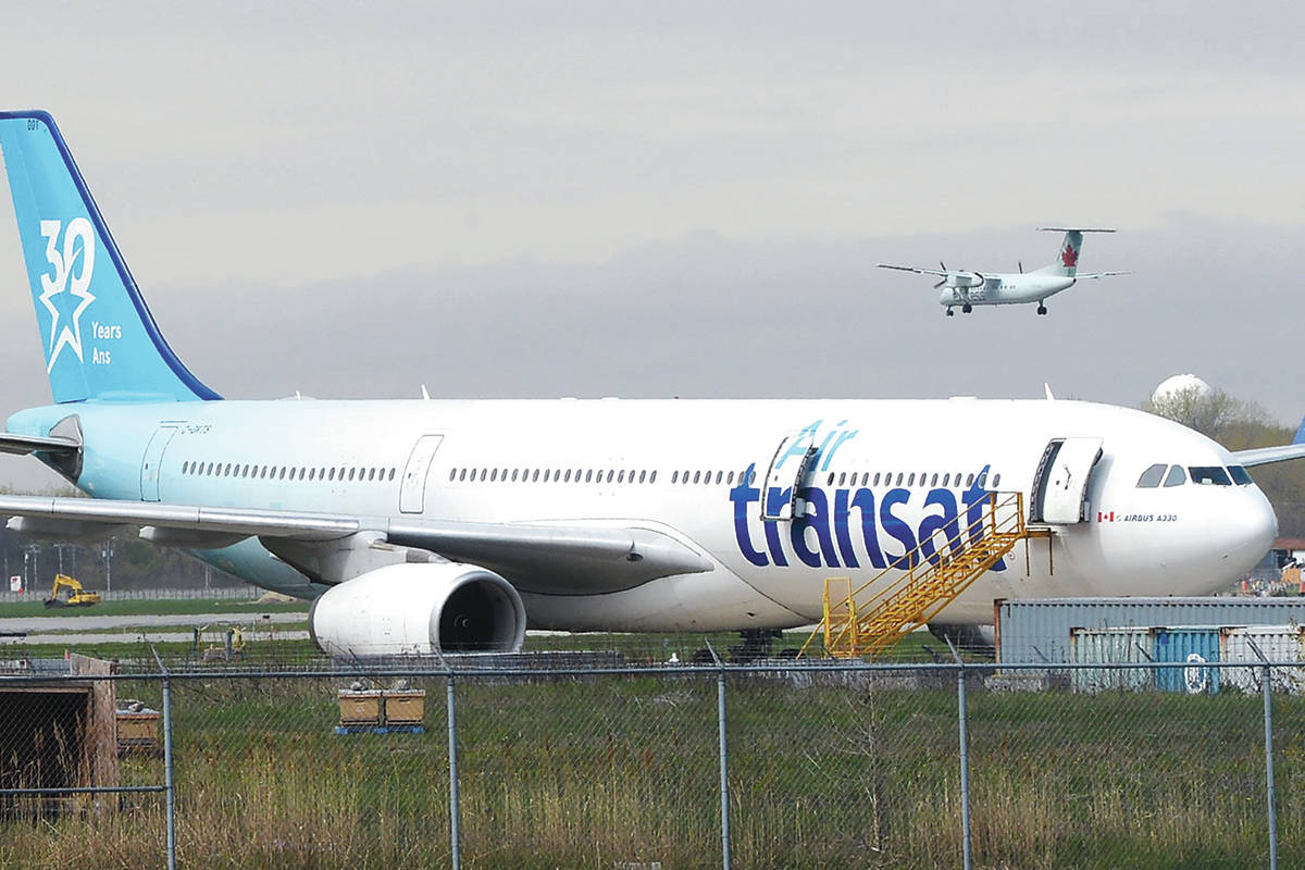 An Air Transat plane is seen as an Air Canada plane lands at Pierre Elliott Trudeau International Airport in Montreal on Thursday, May 16, 2019. THE CANADIAN PRESS/Ryan Remiorz