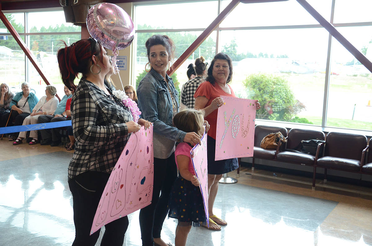 """Michelle (left) and her greeting party hold """"You Found Me"""" signs in anticipation of meeting her biological mother. Photo by Mike Chouinard"""