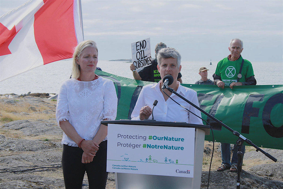Victoria Mayor Lisa Helps is interrupted by protesters as she introduces Environment Minister Catherine McKenna for an announcement of a conservation project, Oak Bay, Aug. 19, 2019. (Black Press Media)