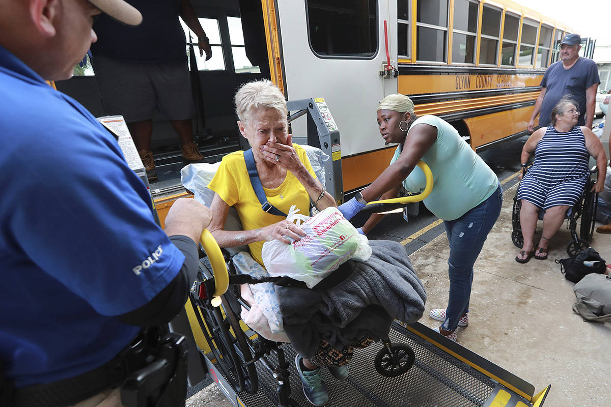 Glynn County school resource officer Mark Hooper, left, and school support staff member Sheree Armstrong, right, help Elizabeth Scales board a special needs bus at Lanier Plaza as hundreds of local residents evacuate the area under mandatory evacuation ahead of Hurricane Dorian, Monday, Sept. 2, 2019, in Brunswick, Ga. (Curtis Compton/Atlanta Journal-Constitution via AP)