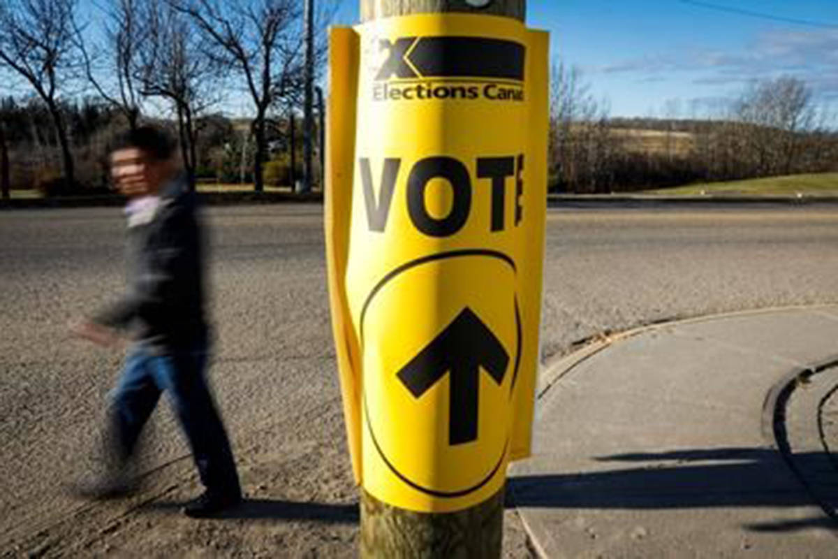 A voter walks past a sign directing voters to a polling station for the Canadian federal election in Cremona, Alta., Monday, Oct. 19, 2015. (Jeff McIntosh/The Canadian Press)