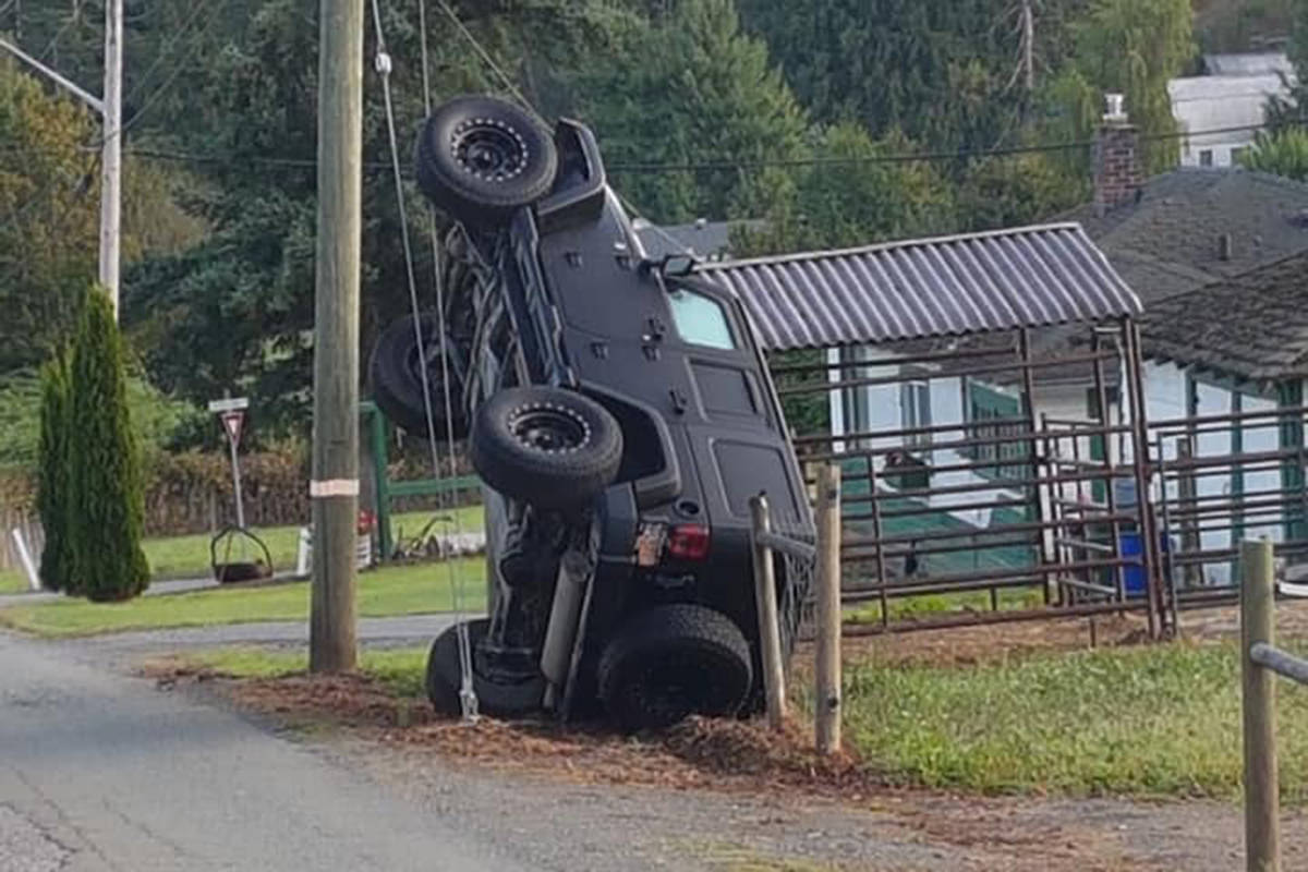 A four-door black Jeep seen on utility pole guy wires on Extrom Road in the Ryder Lake area of Chilliwack on the long weekend. (Facebook)
