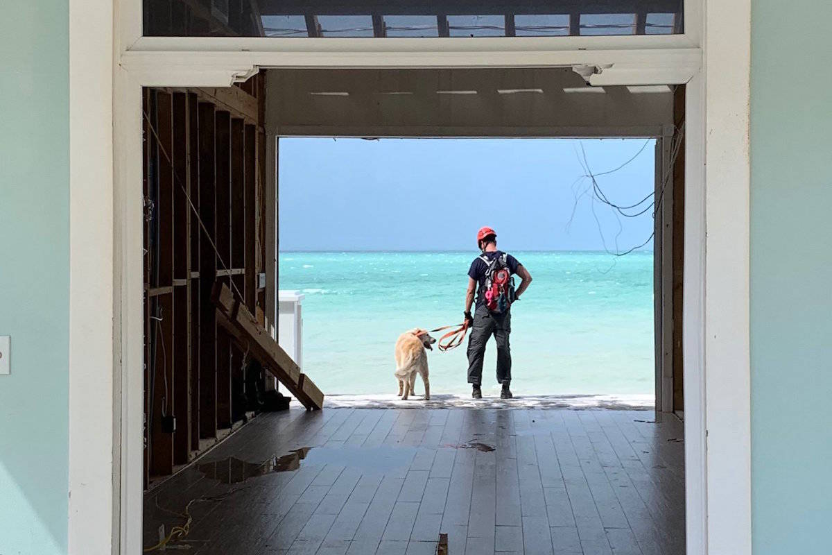 Penticton Fire Chief Larry Watkinson and his disaster dog Sammy take a short break from searching for survivors at Pelican Shore on Great Abaco Island on Sept. 11 after it was decimated by Hurricane Dorian two weeks earlier. (Photo by Burnaby Fire Department)