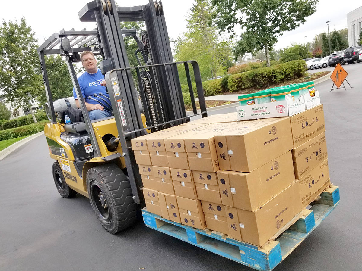 Forklift operator Victor Hatch prepares to load a truck with donations received during the annual Thanksgiving food drive Saturday in Langley. (Dan Ferguson/Langley Advance Times)