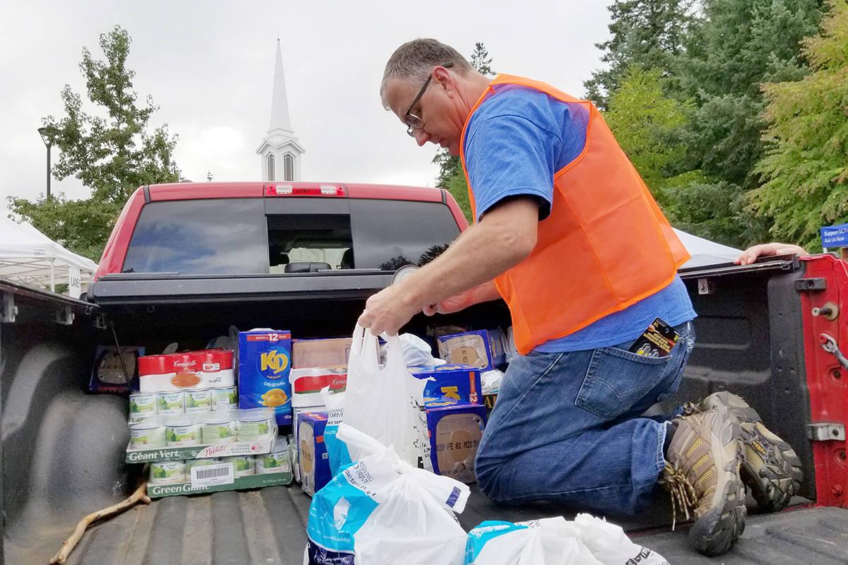 A volunteer helps unload a truck at Thanksgiving food drive. (Dan Ferguson/Langley Advance Times)
