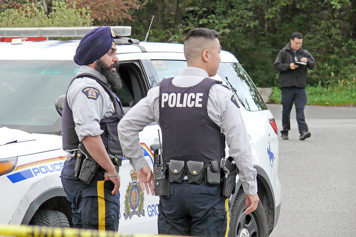 Langley RCMP officers at the site of a fatal shooting outside an Aldergrove McDonalds earlier this month. (Langley Advance Times files)
