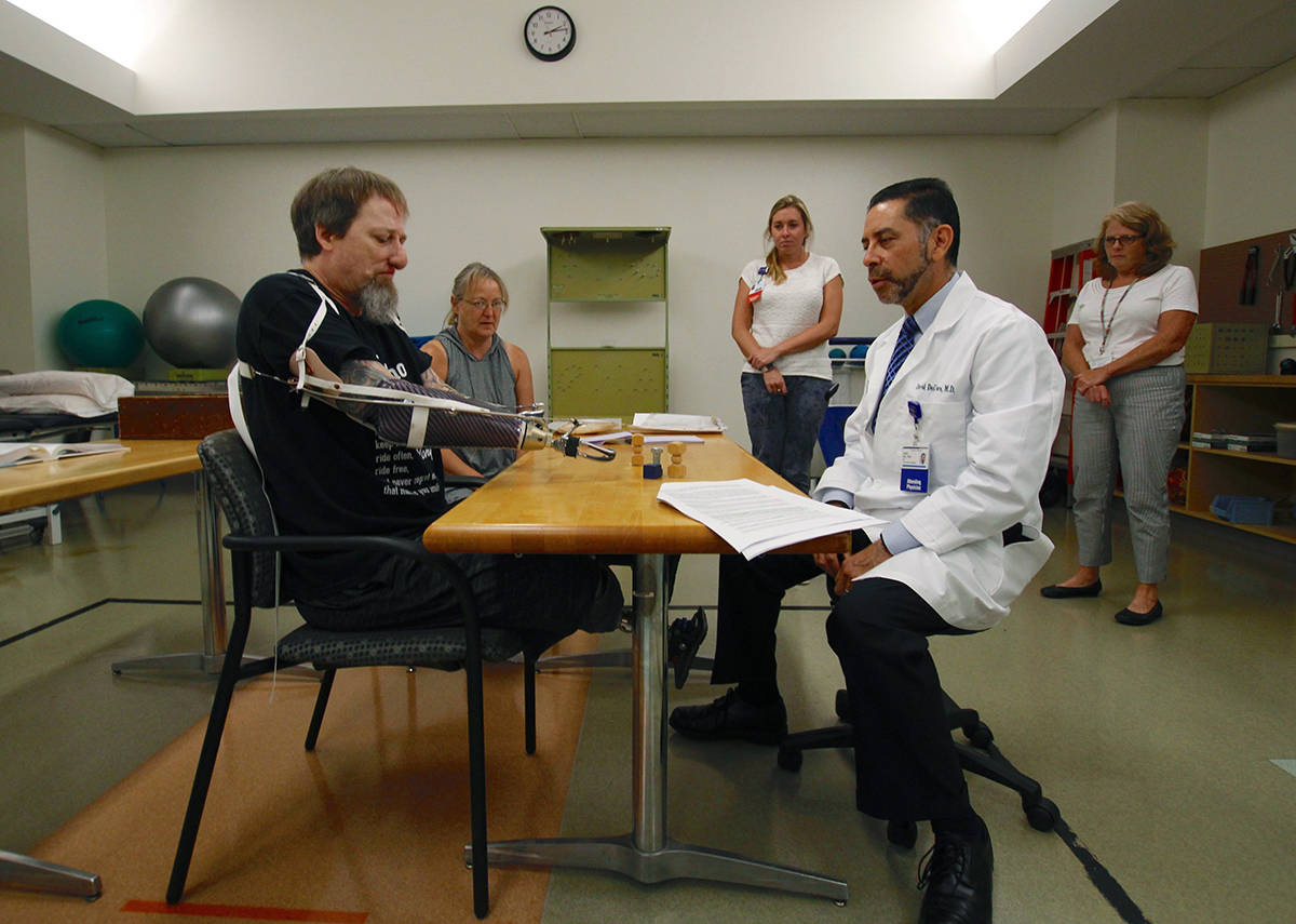 In this Aug. 19, 2019 photo, Greg Manteufel tries out a new prosthetic arm during occupational therapy at Froedtert & the Medical College of Wisconsin in Milwaukee, as he talks to Dr. David Del Toro, the medical director for inpatient rehab. Manteufel lost parts of his arms and legs, as well as the skin of his nose and part of his upper lip from capnocytophaga, a bacteria commonly found in the saliva or cats and dogs that almost never leads to people getting sick, unless the person has a compromised immune system. He was perfectly healthy when he got sick in June of 2018. Over the last seven years, a team of researchers at Brigham and Women's Hospital in Boston, connected to Harvard Medical School, have tested other healthy people who were affected and developed a theory on why they were affected- a gene change in all the victims. (AP Photo/Carrie Antlfinger)