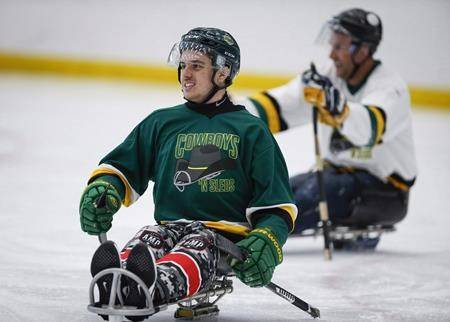 Humboldt Broncos bus crash survivor Ryan Straschnitzki, left, plays in a fund raising sledge hockey game in Calgary on September 15, 2018. A new ad shows a serious Ryan Straschnitzki taping up his hockey stick and pulling on an Adidas jersey before he slides away on an ice sled. (THE CANADIAN PRESS/Jeff McIntosh)
