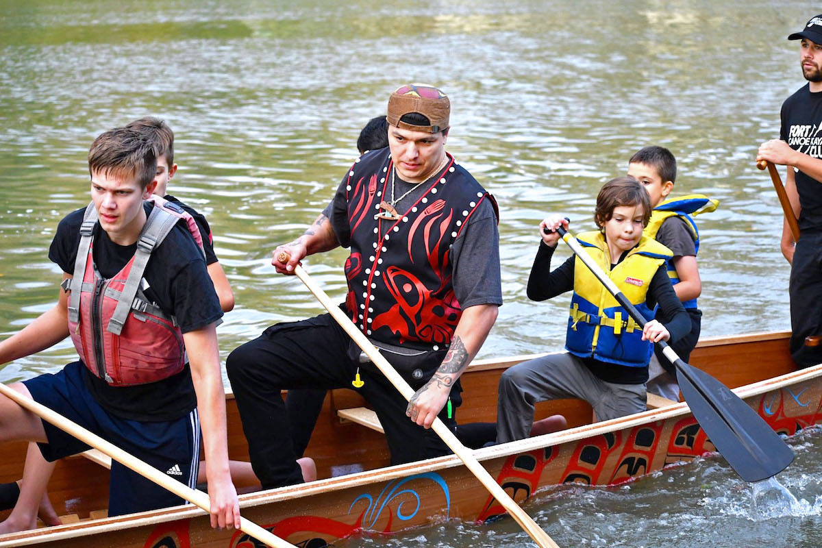 Heiltsuk artist Paul Windsor (middle) accompanied youth from the Fort Langley Canoe and Kayak Club and took out the war canoe on its maiden voyage down the Fraser River last Thursday in Fort Langley. (Special to the Aldergrove Star)