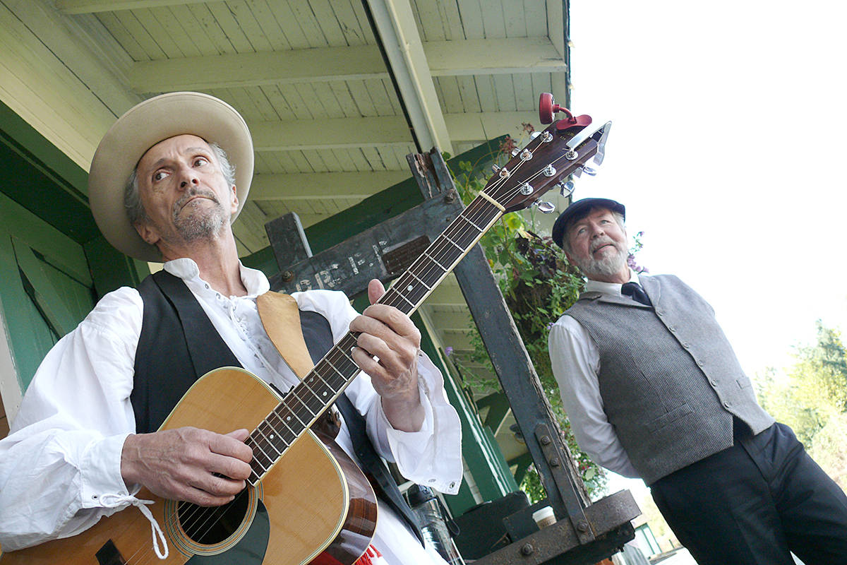 Musician Tom Hammel and performer Paul Cowhig prepare to take an audience on a trip through history at the heritage CN Rail station in Fort Langley. Wheels of Time runs every Saturday until the Cranberry Festival on Oct. 12. (Dan Ferguson/Langley Advance Times)