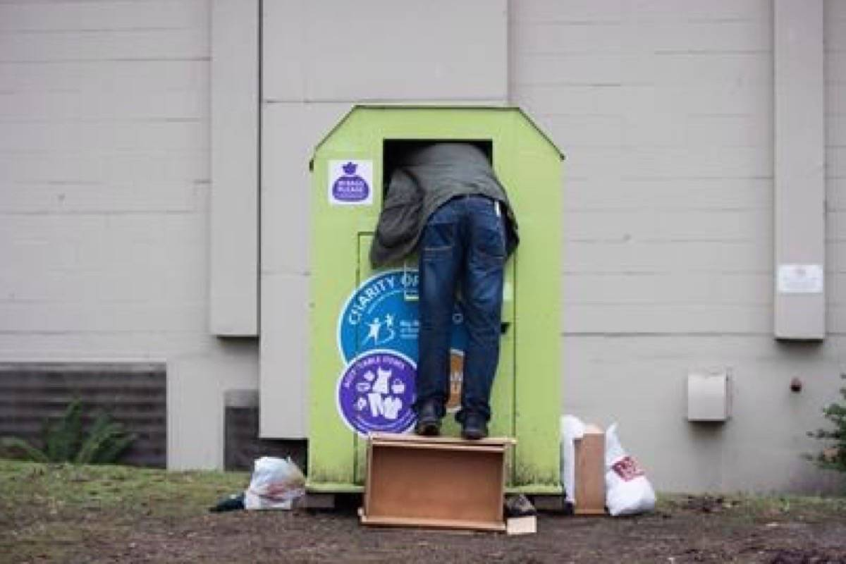 FILE – A man tries to retrieve items from a clothing donation bin in Vancouver. (The Canadian Press)