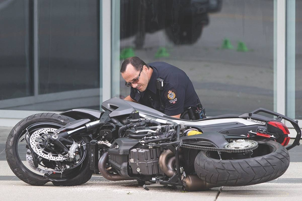 A police officer examines a motorcycle after a female stunt driver working on the movie 'Deadpool 2' died after a crash on set, in Vancouver, B.C., on Monday Aug. 14, 2017. (Darryl Dyck/The Canadian Press)