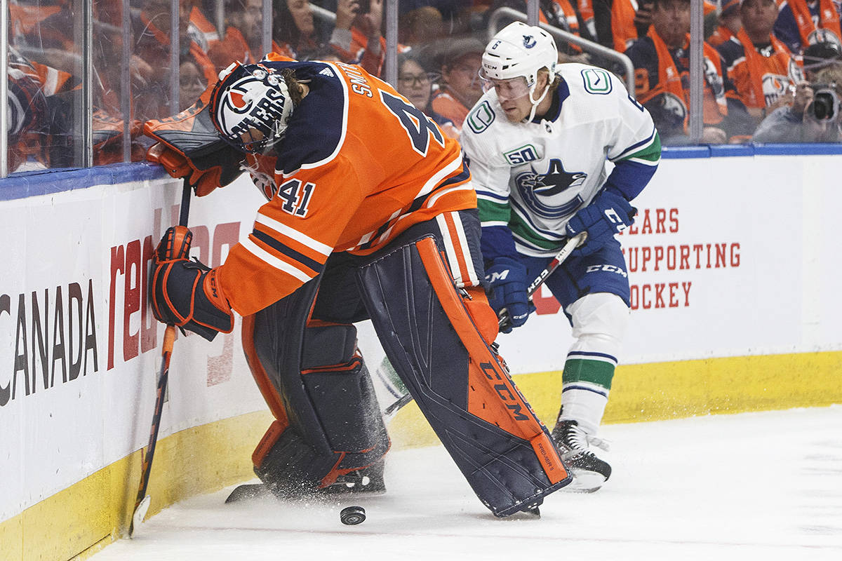 Vancouver Canucks' Brock Boeser (6) and Edmonton Oilers goalie Mike Smith (41) battle for the puck during first period NHL action in Edmonton, Wednesday, Oct. 2, 2019. THE CANADIAN PRESS/Jason Franson