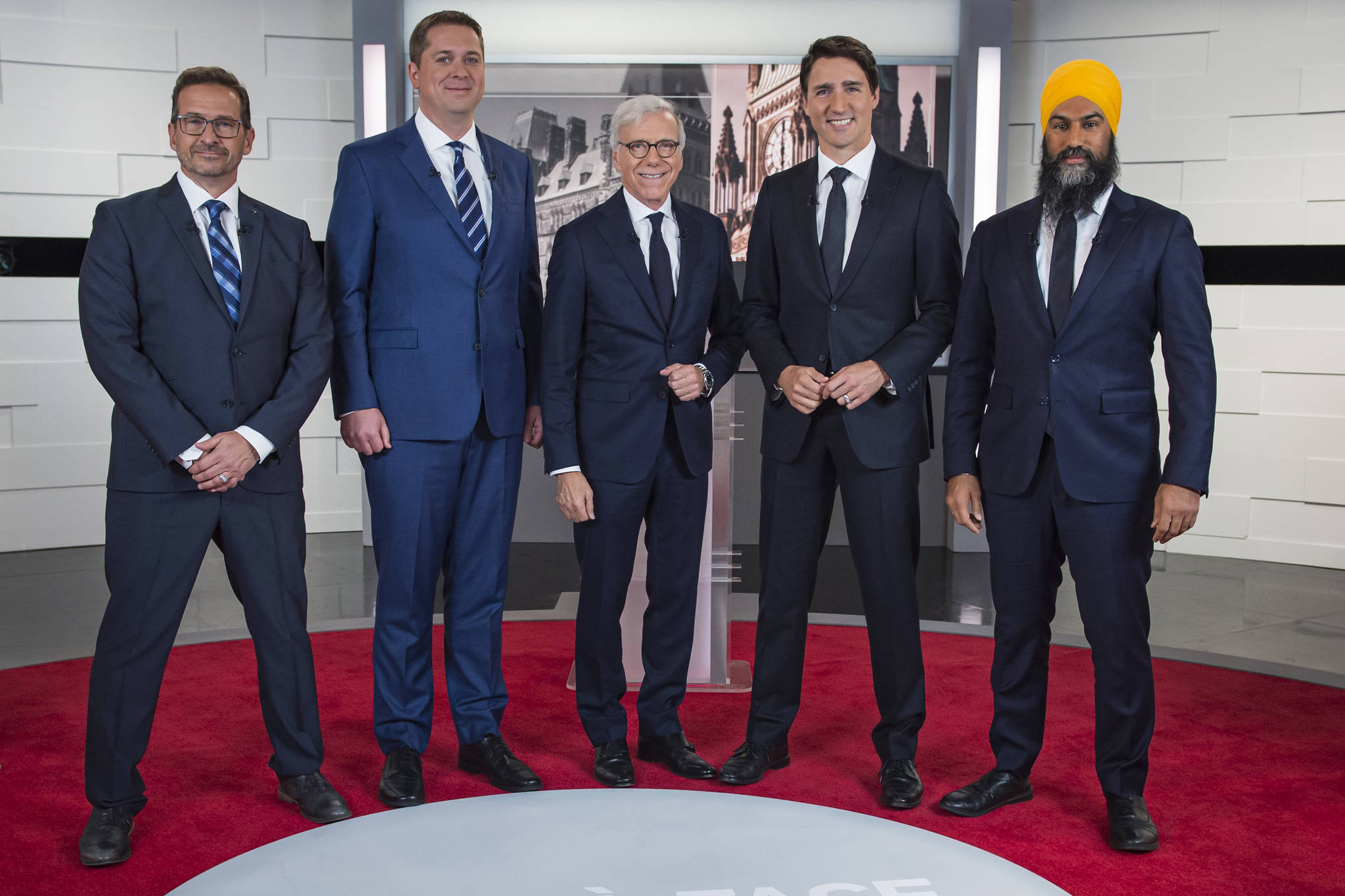 Leader of the Bloc Quebecois Yves-Francois Blanchet, left to right, Conservative Leader Andrew Scheer, TVA host Pierre Bruneau, Liberal Leader Justin Trudeau and NDP Leader Jagmeet Singh pose for a photo at the TVA french debate for the 2019 federal election, in Montreal, Wednesday, Oct. 2, 2019. (THE CANADIAN PRESS/Joel Lemay)