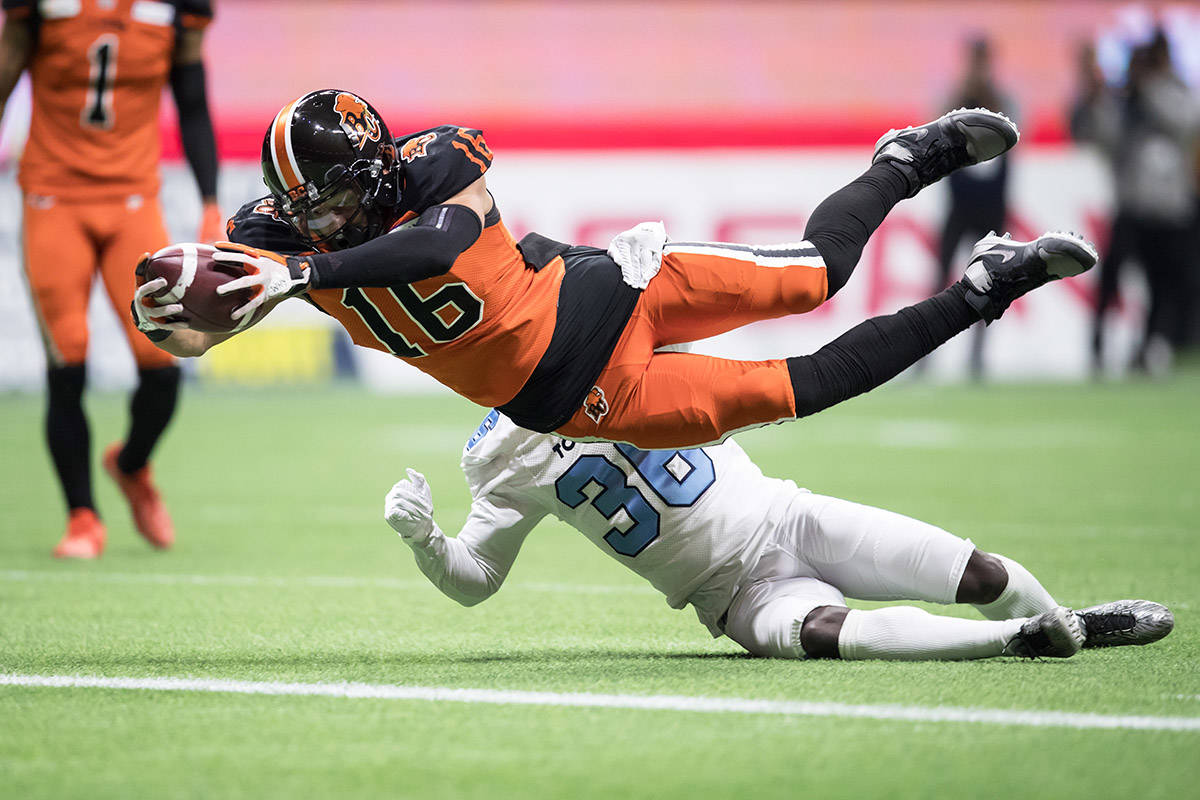B.C. Lions' Bryan Burnham (16) dives across the goal line to score a touchdown in front of Toronto Argonauts' Trumaine Washington, back, after making a reception during first half CFL football action in Vancouver, Saturday, Oct. 5, 2019. THE CANADIAN PRESS/Darryl Dyck