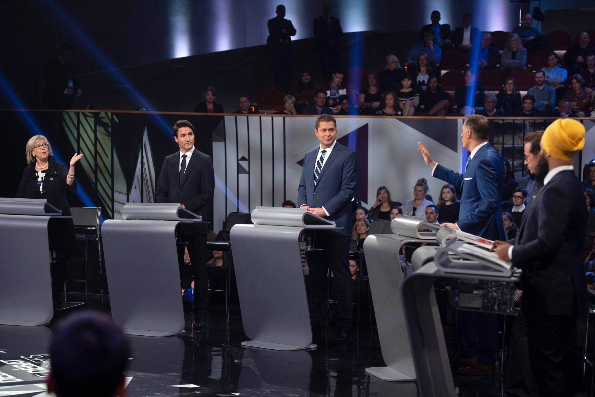 Green Party leader Elizabeth May, left, and People's Party of Canada leader Maxime Bernier, third from right, exchange ideas as Liberal leader Justin Trudeau, Conservative leader Andrew Scheer, Bloc Quebecois leader Yves-Francois Blanchet and NDP leader Jagmeet Singh look on during the Federal leaders debate in Gatineau, Que. on Monday, October 7, 2019. THE CANADIAN PRESS/Justin Tang