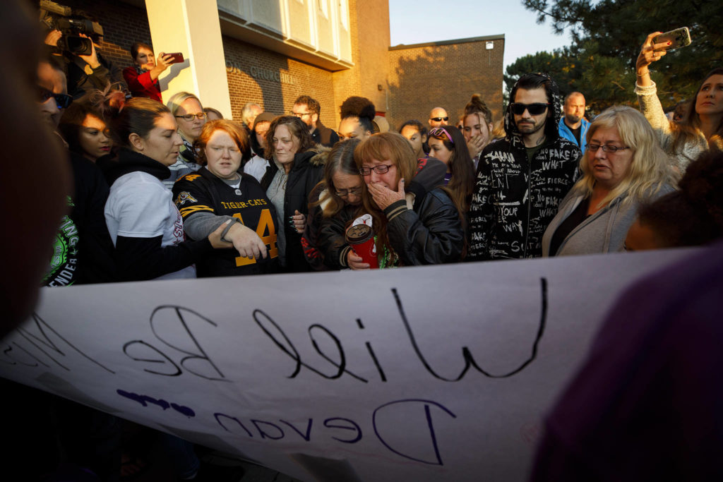 Shari-Ann Bracci-Selvey, centre, fights back tears at a vigil for her 14-year-old murdered son, Devan Selvey, at his high school, Sir Winston Churchill Secondary School, In Hamilton, Ont., Wednesday, Oct. 9, 2019. THE CANADIAN PRESS/ Cole Burston