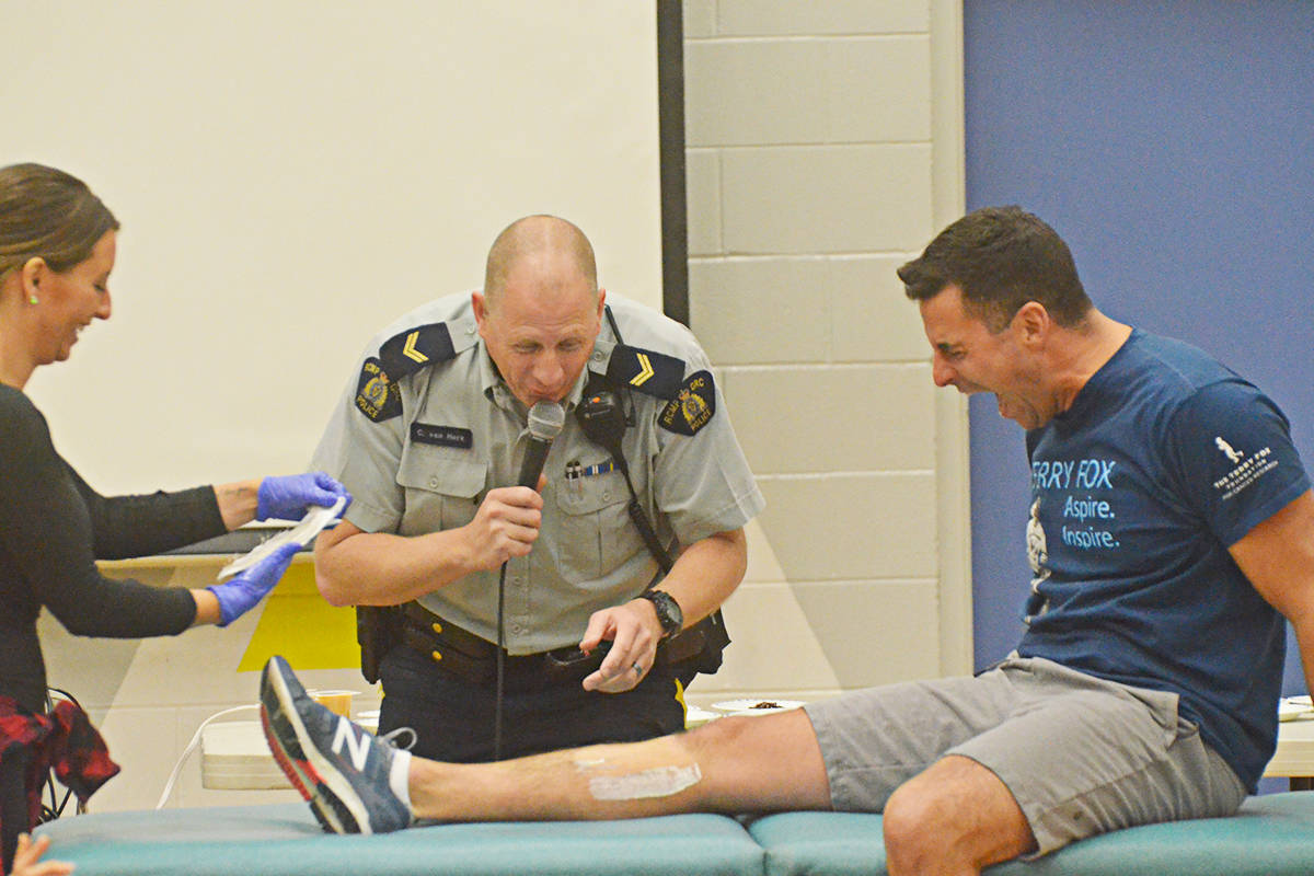 Parent Dana Bishop waxed Alice Brown Elementary principal Michael Carlyle's legs as Langley RCMP Cpl. Craig van Herk looked on Wednesday. (Matthew Claxton/Langley Advance Times)