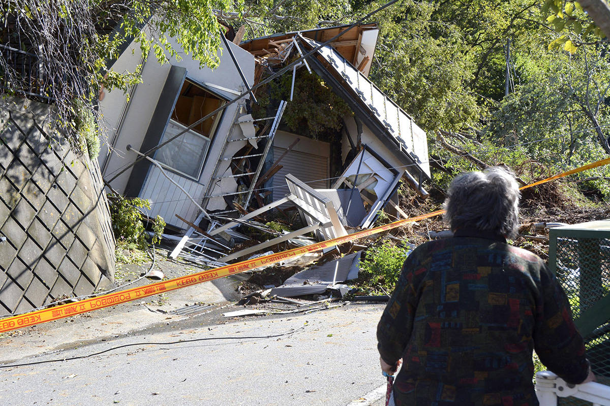 People look at the house damaged by landslide caused by Typhoon Hagibis in Sagamihara, near Tokyo, Japan, Sunday, Oct. 13, 2019. Rescue efforts for people stranded in flooded areas are in full force after a powerful typhoon dashed heavy rainfall and winds through a widespread area of Japan, including Tokyo.(Kyodo News via AP)
