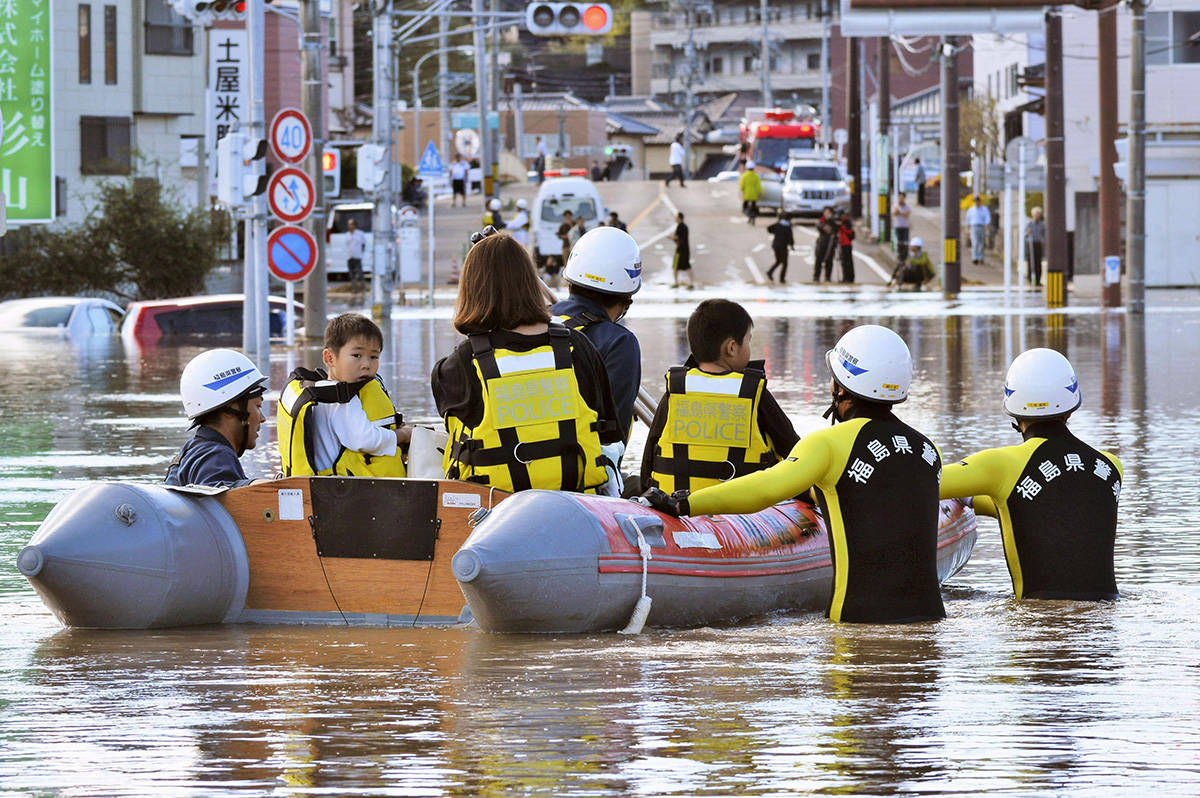 Residents on a rubber boat are rescued as they were stranded by Typhoon Hagibis, in Iwaki, Fukushima prefecture, northern Japan, Sunday, Oct. 13, 2019. Rescue efforts for people stranded in flooded areas are in full force after a powerful typhoon dashed heavy rainfall and winds through a widespread area of Japan, including Tokyo.(Kyodo News via AP)