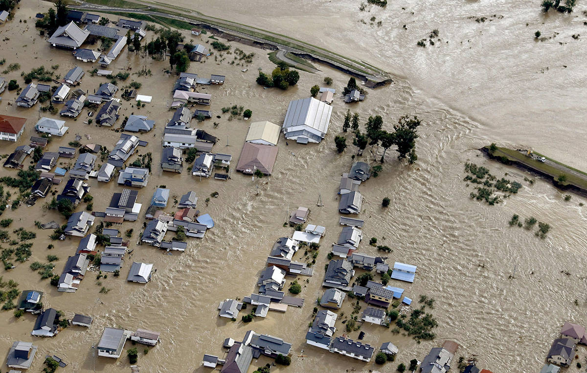 Residential area, center, are submerged in muddy waters after an embankment of the Chikuma River, top right, broke because of Typhoon Hagibis, in Nagano, central Japan, Sunday, Oct. 13, 2019. Rescue efforts for people stranded in flooded areas are in full force after a powerful typhoon dashed heavy rainfall and winds through a widespread area of Japan, including Tokyo.(Yohei Kanasashi/Kyodo News via AP)