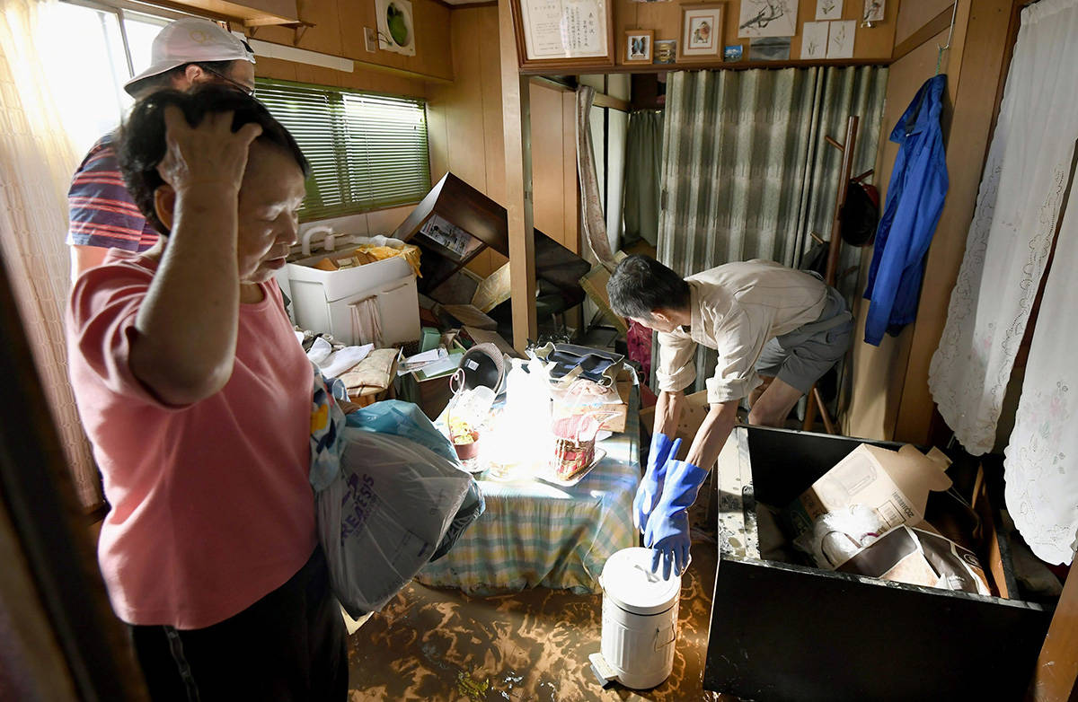 People clean their house after Typhoon Hagibis hit the area in Kawasaki, near Tokyo, Japan, Sunday, Oct. 13, 2019. Rescue efforts for people stranded in flooded areas are in full force after a powerful typhoon dashed heavy rainfall and winds through a widespread area of Japan, including Tokyo.(Yohei Nishimura/Kyodo News via AP)