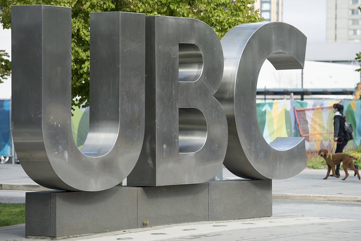 A woman and her dog walks past the UBC sign at the University of British Columbia in Vancouver, Tuesday, Apr 23, 2019. THE CANADIAN PRESS/Jonathan Hayward