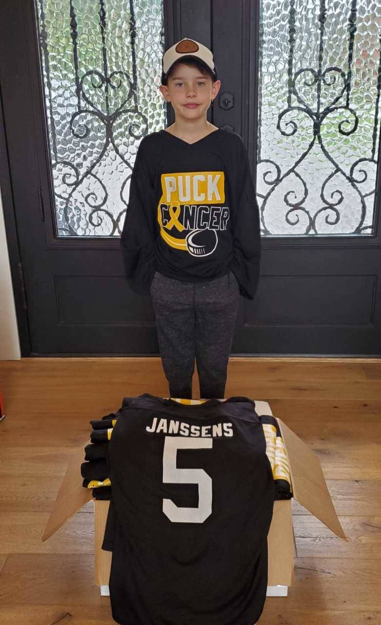 Fisher Barker, an Atom player in the Langley Minor Hockey Association shows off the jerseys donated by the Barker family and Levy's Source for Sports for the fundraiser Sunday, Oct. 20 in support of Markus Janssens. (Tannis Holm/Special to the Langley Advance Times)