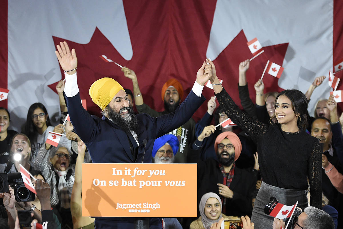 NDP leader Jagmeet Singh and his wife Gurkiran Kaur wave to supporters on stage at NDP election headquarters in Burnaby, B.C. on Monday, Oct. 21, 2019. THE CANADIAN PRESS/Nathan Denette