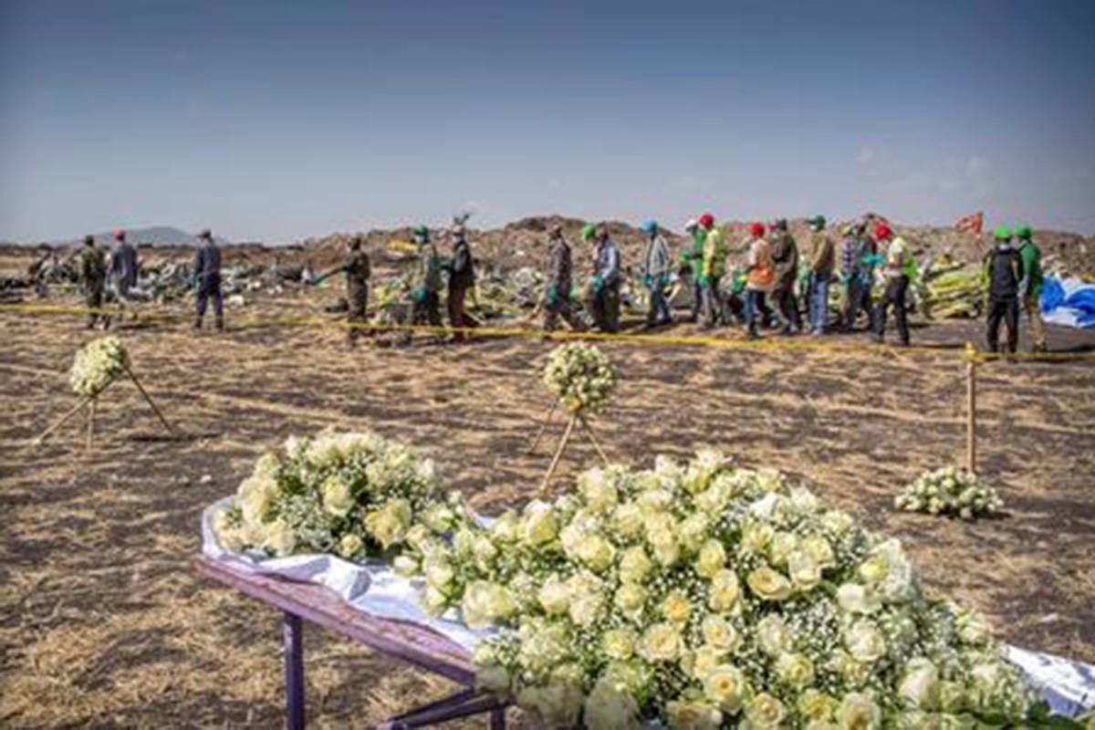Workers walk past flowers laid at the scene where the Ethiopian Airlines Boeing 737 Max 8 crashed shortly after takeoff on Sunday killing all 157 on board, near Bishoftu, or Debre Zeit, south of Addis Ababa, in Ethiopia Wednesday, March 13, 2019. THE CANADIAN PRESS/AP-Mulugeta Ayene