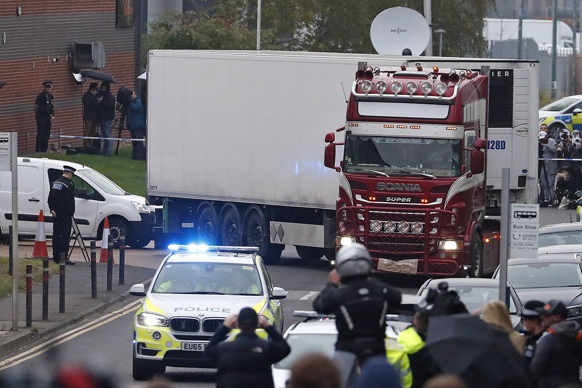 Police escort the truck, that was found to contain a large number of dead bodies, as they move it from an industrial estate in Thurrock, south England, Wednesday Oct. 23, 2019. Police in southeastern England said that 39 people were found dead Wednesday inside a truck container believed to have come from Bulgaria. (AP Photo/Alastair Grant)