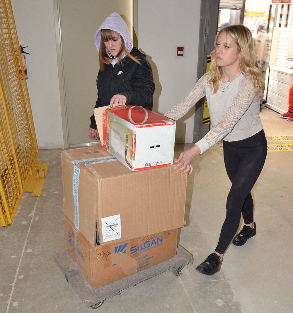 KC Mcmahon and Trinity Nyari are some of the Vanguard Secondary students who helped set up the Langley Christmas Bureau this holiday season. (Heather Colpitts/Langley Advance Times)