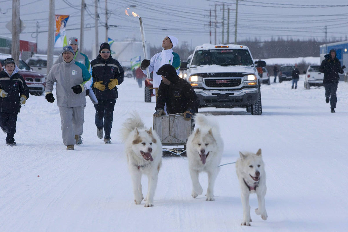 Torchbearer Lukasi Tukkiapik is seen carrying the Olympic Flame on a dogsled in Kuujjauq, Que. Tuesday, Nov. 10, 2009. The Olympic Flame which traveled all the way from Olympia in Greece is now on a 106 day cross country relay which will end in Vancouver on Feb. 12, 2010 to mark the start of the Vancouver 2010 Winter Olympic Games. THE CANADIAN PRESS/Jonathan Hayward