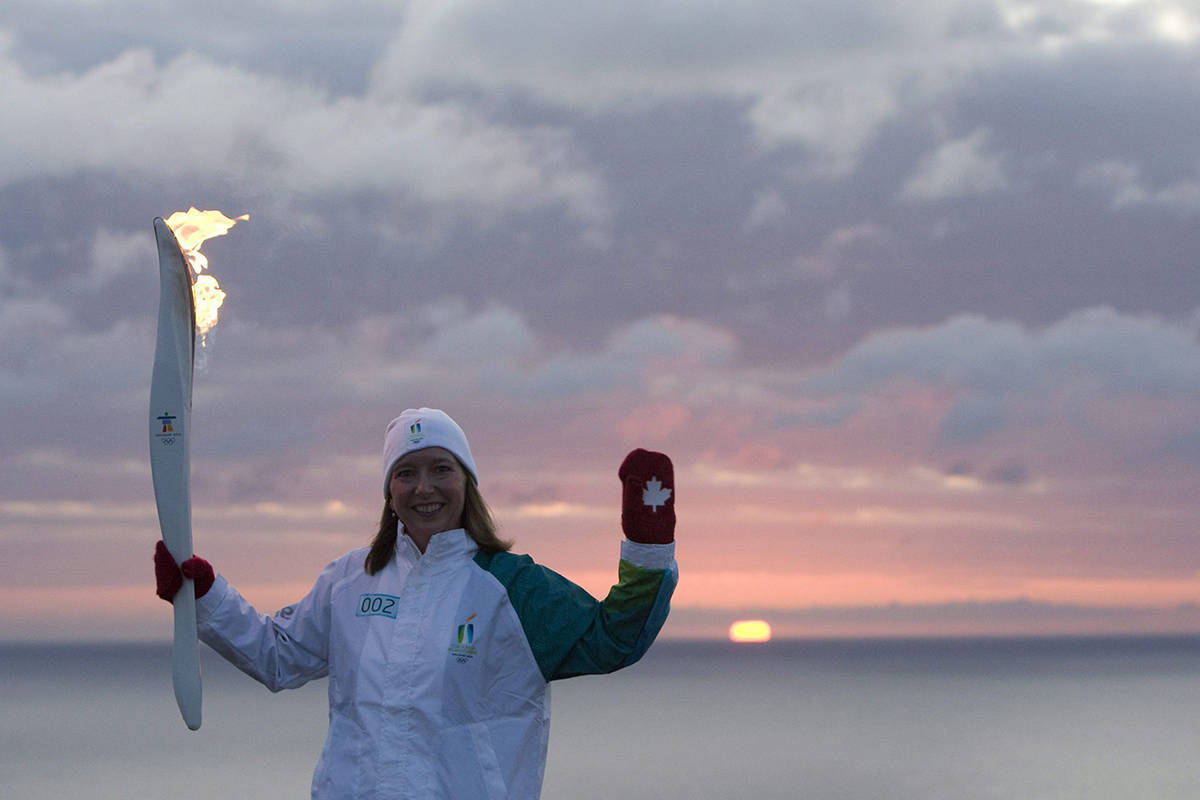 Torchbearer Donna O'Grady holds up the Olympic Flame as the sun rises over the Atlantic Ocean at Cape Spear, NL, Friday, Nov. 13, 2009. Cape Spear is the most easternly point in Canada and North America. The Olympic Flame which traveled all the way from Olympia in Greece is now on a 106 day cross country relay which will end in Vancouver on Feb. 12, 2010 to mark the start of the Vancouver 2010 Winter Olympic Games. THE CANADIAN PRESS/Jonathan Hayward