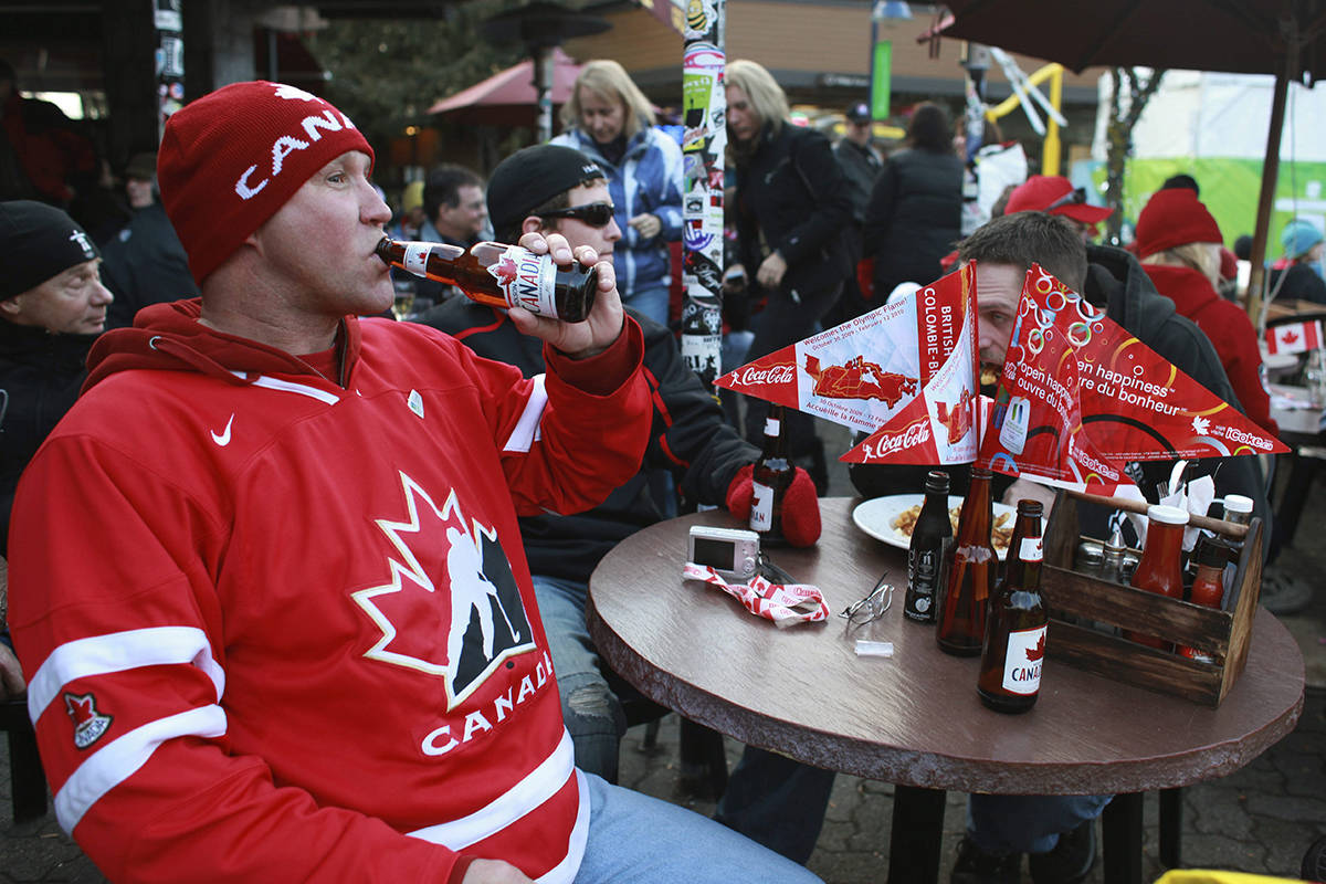 A man dressed in the Canadian national Icehockey team jersey enjoys a beer in down town Whistler, British Columbia, as people celebrate the Olympic torch arrival, Friday, Feb. 5, 2010. (AP Photo/Ricardo Mazalan)